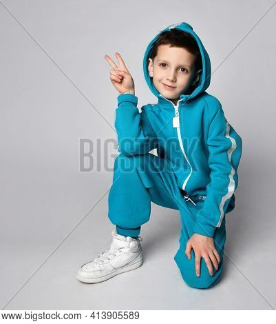 Fashion Boy Child In Warm Sportswear Suit Kneeing Gesturing Victory Looking At Camera. Male Kid Adve