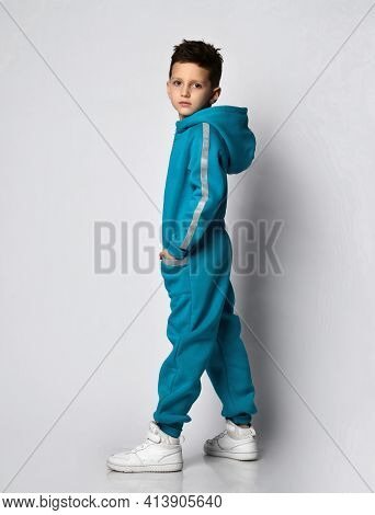 Fashion Boy Child In Warm Sportswear Suit Standing Half Turn Looking At Camera. Male Kid Advertising