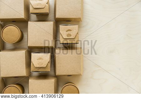 Flat Lay Of Kraft Paper Or Cardboard Eco Packages On Wooden Background