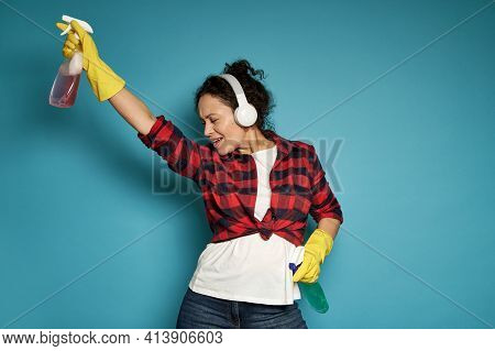 Hispanic Woman, Housewife, With Headphones Holding Cleaning Sprays In Her Hands And Dancing With Her
