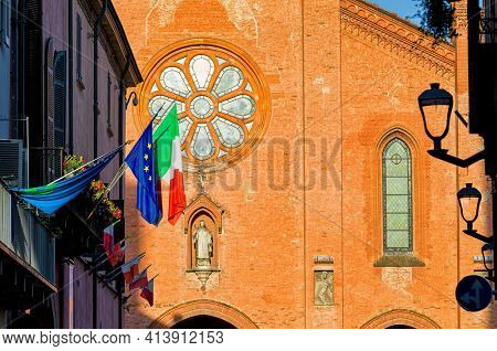 Facade of the San Lorenzo Cathedral lit by sunlight in small town of Alba in Piedmont, Northern Italy.