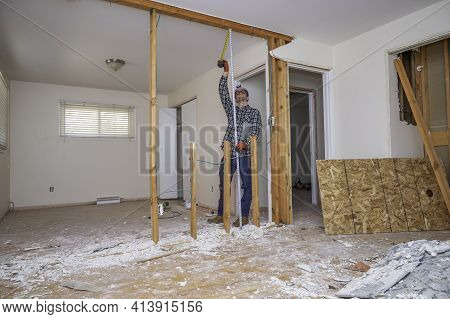 Carpenter Measuring A Room That Has Had The Drywall And Flooring Demolished For A Home Renovation Pr