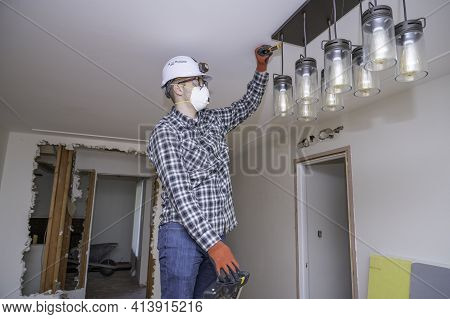Electrician Testing Electrical Current On A Lighting Fixture During A Home Remodel.