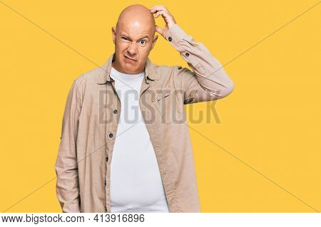 Middle age bald man wearing casual clothes confuse and wonder about question. uncertain with doubt, thinking with hand on head. pensive concept.