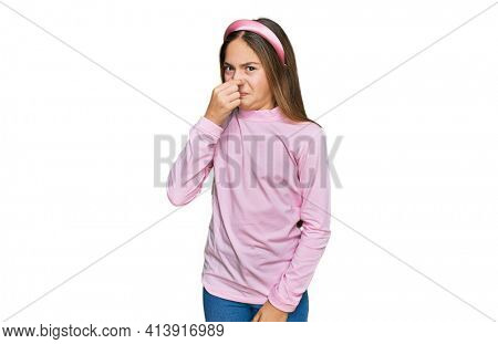 Beautiful brunette little girl wearing casual turtleneck sweater smelling something stinky and disgusting, intolerable smell, holding breath with fingers on nose. bad smell