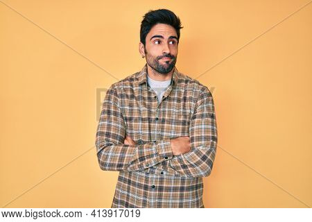 Handsome hispanic man with beard wearing casual clothes smiling looking to the side and staring away thinking.