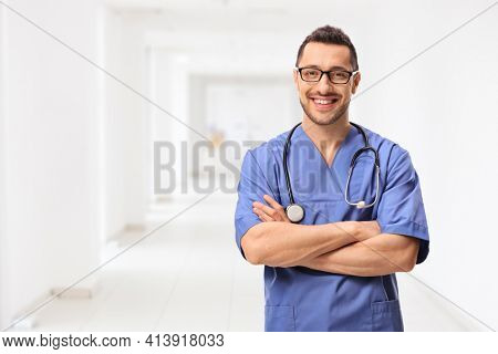 Young male health care worker posing in a hospital corridor