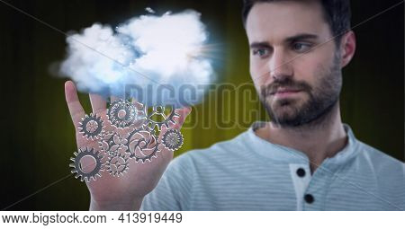 Composition of network of digital cogs with white cloud over hand of man. global technology and digital interface concept digitally generated image.