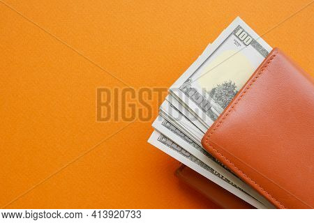 100 Dollar In Wallet On Orange Paper Background For Travel Summer In Holidays. Planing Earn Money In