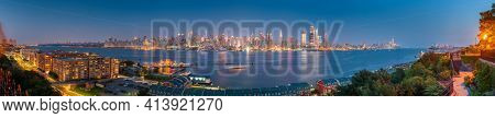 New York, New York, USA Midtown Manhattan skyline on the Hudson River at night.