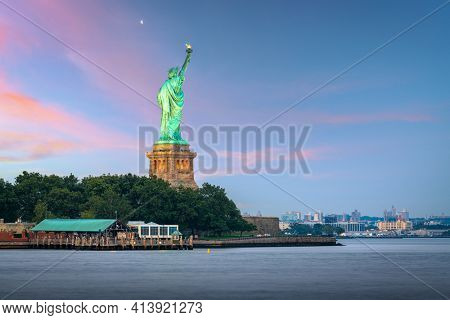 Statue of Liberty in New York Harbor at dusk.