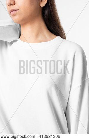 Woman in white long sleeve tee men's fashion studio portrait
