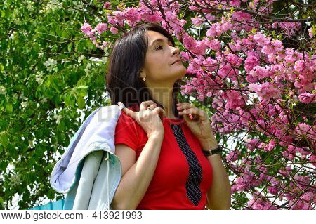 Portrait Of 45 Y.o. Russian Woman Sniffing Sakura Branch On Background Of Blooming Apple Tree In Spr