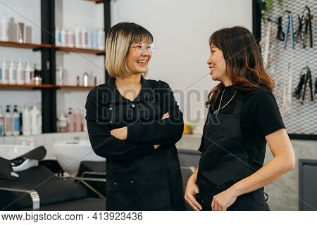 Happy Young Asian Female Hairstylist Colleagues Working In Salon Standing Wearing Apron And Spectacl