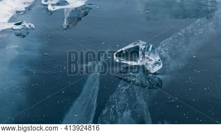 A Transparent Piece Of Ice Of A Bizarre Shape Lies On The Thick Blue Ice With Cracks. Mirror Reflect