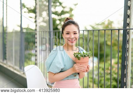 Green Plants In Pot In Beautiful Happy Asian Woman Hands On Balcony At Apartment In The Morning