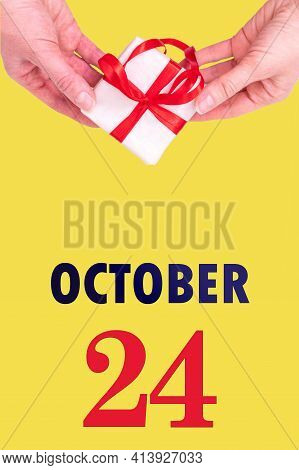 October 24th. Festive Vertical Calendar With Hands Holding White Gift Box With Red Ribbon And Calend
