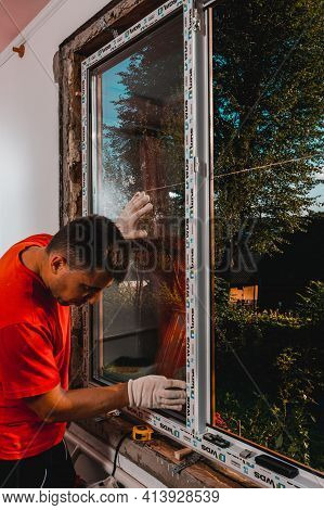 Dolyna, Ukraine July 31, 2020: An Employee Installs A Window In The House, Installation Of A Plastic