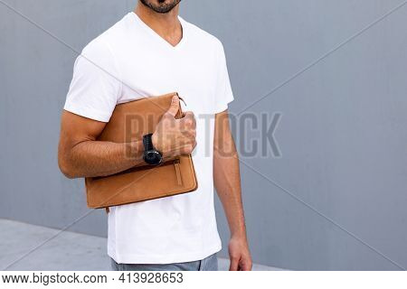 Man holding clutch walking in the city
