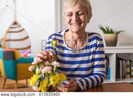 Senior people lifestyle. Senior woman relaxing at home while organizing flowers in vase. Senior woman domestic lifestyle. Lifestyle. Lifestyle of senior people at home. Pandemic lockdown lifestyle.