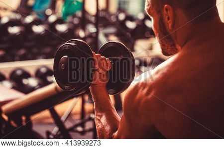Man Lifting Dumbbell In A Gym Making Exercise For Muscles. Bodybuilder Working Out With Dumbbell Wei