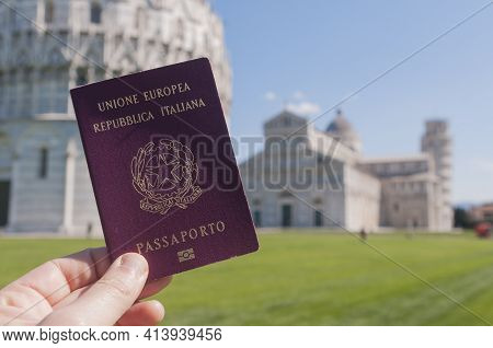 Man Hold An Italian Passport In Front Of The World Famous Leaning Tower Of Pisa