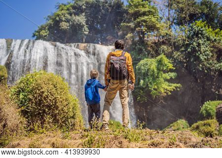 Dad And Son Tourists On The Background Of Elephant Waterfall Near Dalat City In Vietnam