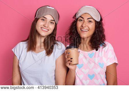 Satisfied Females Posing Isolated Over Rose Background, Wearing Pajamas And Sleeping Masks, Having G