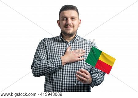 White Guy Holding A Flag Of Benin And Holds His Hand On His Heart Isolated On A White Background Wit
