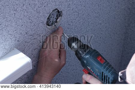 A Man With Glasses Fixes A Ceramic Socket In A Hole In The Wall Using An Electric Drill, Installing
