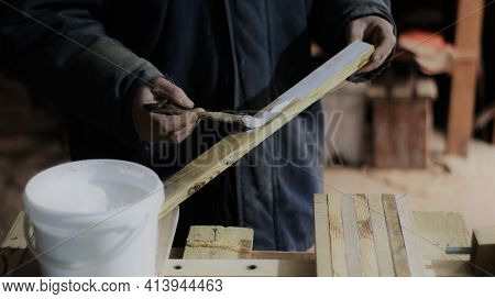 Applying Glue To A Narrow Wooden Plank In The Process Of Creating A Wood Product In The Atmosphere O