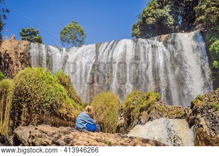 Mother And Son Tourists On The Background Of Elephant Waterfall Near Dalat City In Vietnam