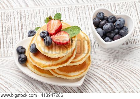Healthy breakfast with pancakes. Homemade american pancakes with berries and honey on wooden table