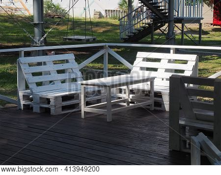 White Bench And Table From Old Wooden Warehouse Pallets Stand On A Wooden Veranda In The Park