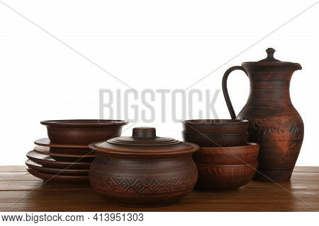 Different Clay Dishware On Wooden Table Against White Background
