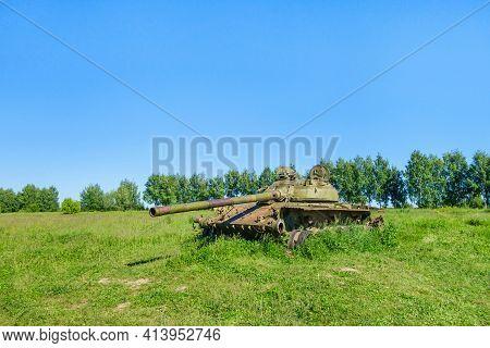 Remains Of Battle Panzer In Field. Summer Weather, Green Field Around