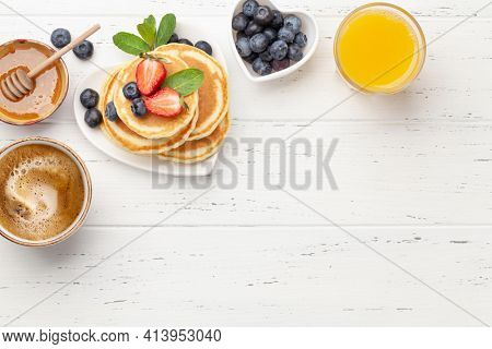 Breakfast with pancakes, orange juice and espresso coffee. Homemade american pancakes with berries and honey. Top view flat lay with copy space