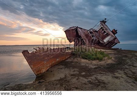 An Old Abandoned Ship On The Shore Of The Drying Up Aral Sea. Kazakhstan. Abandoned Ships Sawn For S