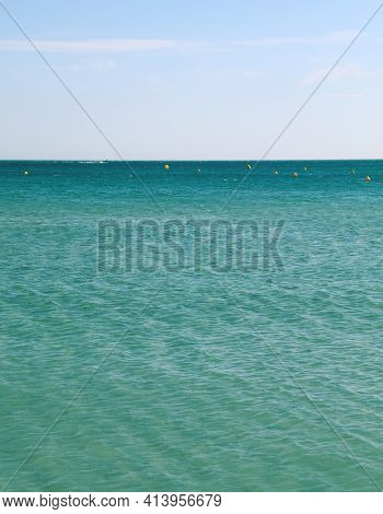 Tranquil Seascape With Calm Turquoise Sea Water Ripples And Waves Under Clear Day Blue Sky, High Ang
