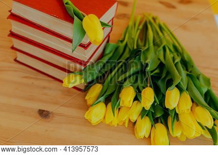 Bright Fresh Yellow Tulips On Wooden Table. Bunch Of Tulips And Many Books. Flowers On Pile Of Books