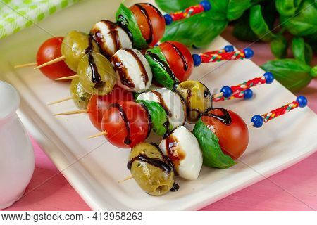 Caprese Skewers With Cherry Tomato, Mini Mozzarella Balls And Olives With Balsamic Drizzle