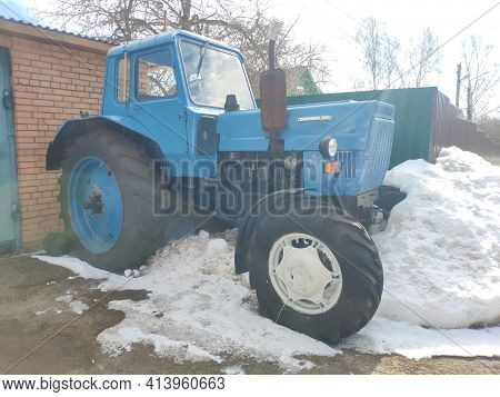 Blue Tractor In The Snow. Old Rusty Tractor In The Parking Lot In Winter