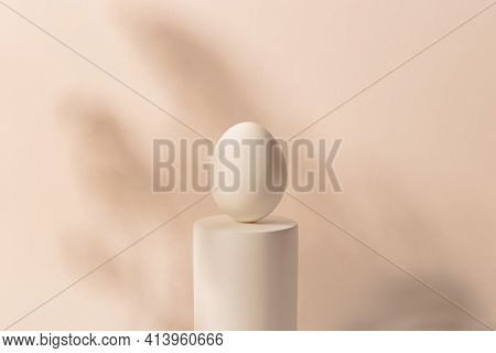 One White Easter Egg On A Podium Against A Neutral Background. Minimalism And Simplicity Aesthetics