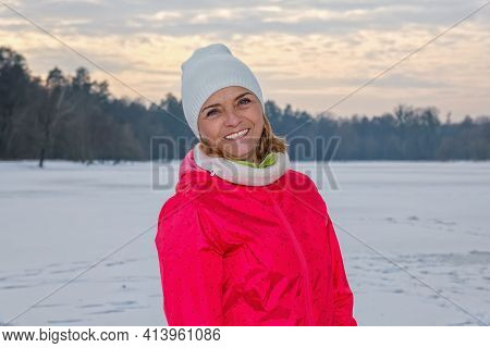 Elderly Woman In White Knitted Hat Standing In Winter Forest, Resting After Exercise And Looking At