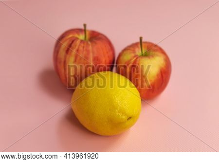 In The Horizontal Photo, In The Center On A Pink Background, Two Ripe Gala Apples And One Lemon. App