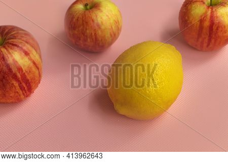 In The Horizontal Photo, On A Pink Background, Three Ripe Gala Apples And One Lemon. Apples And Lemo