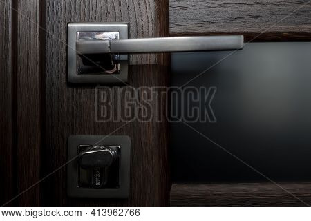 Doorknob And Latch On Dark Wooden Door. The Picture Is In A Low Key. View From The Front.