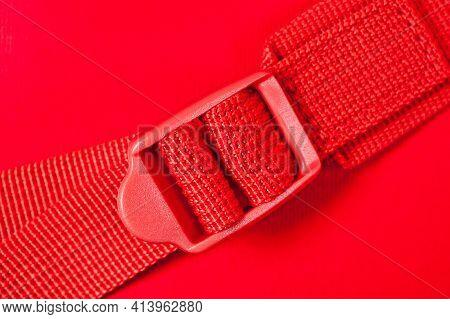 Fabric Belt With Regulator Buckle Against An Orange Fabric Background.
