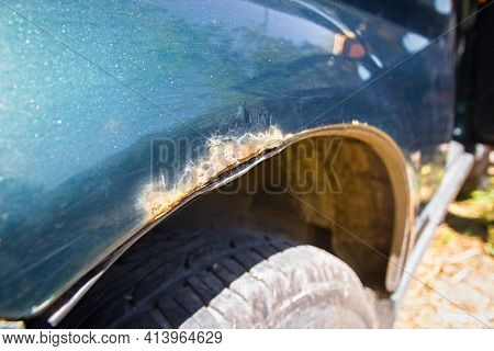 Close-up Detail Of A Rusty Fender Of A Green Car.