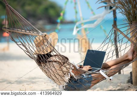 Lifestyle Freelance Woman Using Laptop Working And Relax On The Beach. Asia People On Hammock Succe